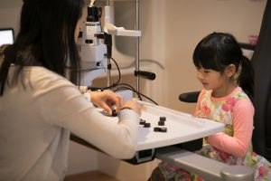 Child identifying shapes and images as part of eye test
