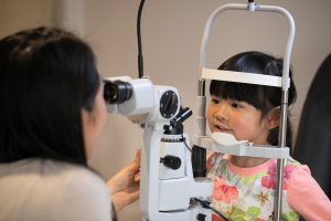 Smiling child receiving an eye test from one of our team members