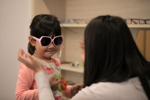 Young girl trying on pink Australian certified UV protection sunglasses